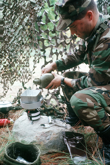 First LT. Michael D. Bramhall of Detachment 3, 5th Weather Squadron, heats some water on a field stove during the XVIII Airborne Corps command post Exercise Caber Dragon '89