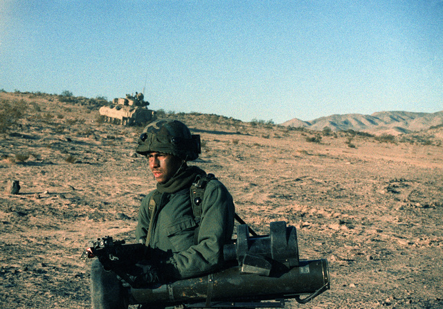 A soldier of the 24th Infantry Division (Mechanized) wearing multiple integrated laser engagement system (MILES) gear moves across the face of a hill during an exercise at the National Training Center. The soldier is carrying an M16 rifle equipped with an M203 grenade launcher and an M47 Dragon anti-tank weapon field handling trainer