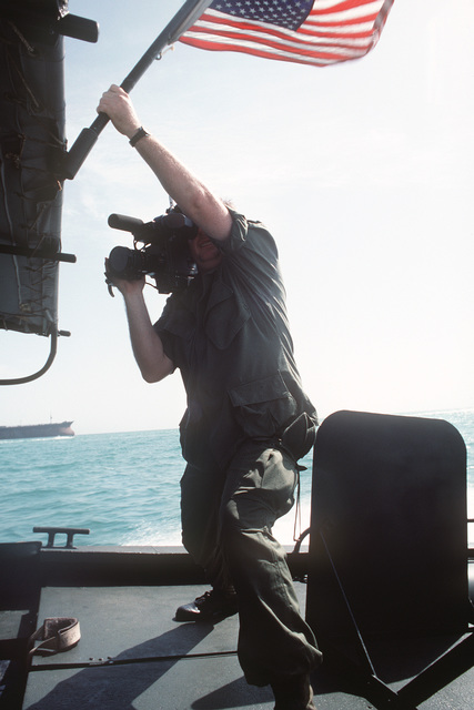 Aboard a PBR Mark 2 riverine patrol boat, a cameraman grasps the flag mast for stability as he attempts to film while the boat is underway. The patrol boat is among the Navy assets being used to provide security for US-flagged shipping in the gulf
