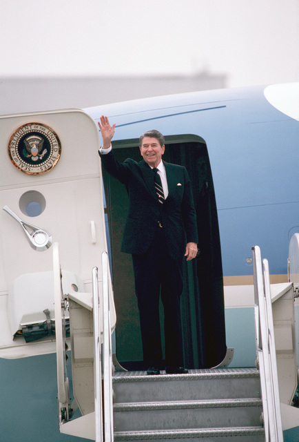 President Ronald Regan waves from the doorway of Air Force One as he prepares to depart from the base following a stopover on his way to San Bernardino, California (CA)
