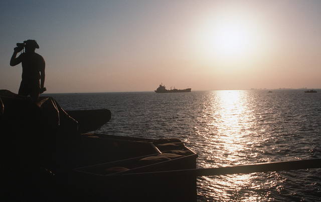Silhouetted by the setting sun, a lookout on the barge WIMBROWN 7 peers through a pair of binoculars as a commercial vessel passes by. The barge is being used in support of Navy efforts to provide security for US-flagged shipping in the gulf