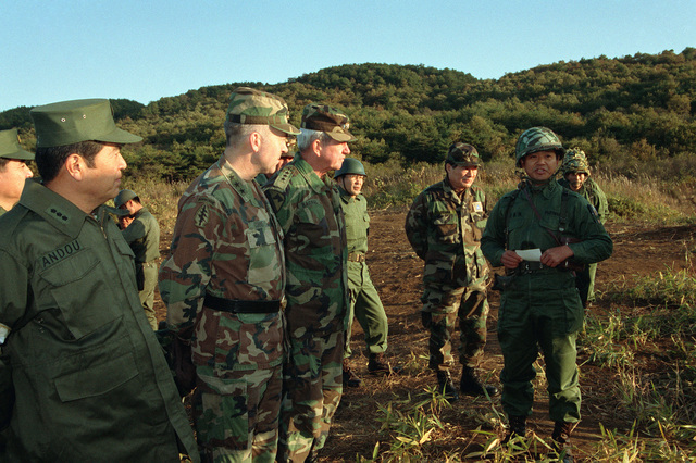 Listening to a Japanese Self Defense Force officer are, from left to right, Lieutenant General (LGEN) Andou Katsuhiko, commander, 6th Infantry Division, Japanese Self Defense Forces; LGEN Johnnie H. Corns, commander, US Army Japan/IX Corps; and LGEN Charl