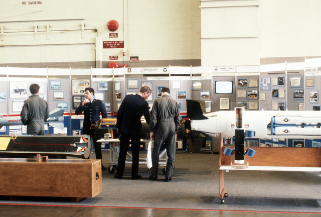 Air Force officers browse through a defense contractor's exhibit in a hangar during the Strategic Air Command (SAC) bombing and navigation competition Proud Shield '88