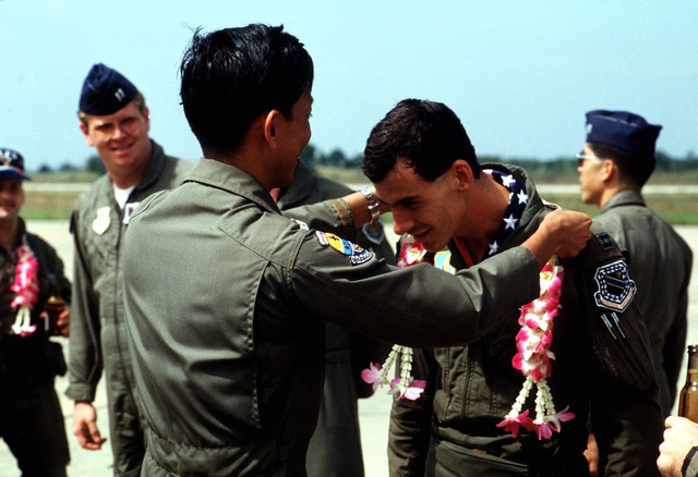 Wing Commander Putti, Royal Thai Air Force, presents Captain James Lewis, 3rd Tactical Fighter Squadron, with a lei upon Lewis's arrival on base to take part in the joint US/Royal Thai Air Force Exercise COMMANDO WEST 89-1