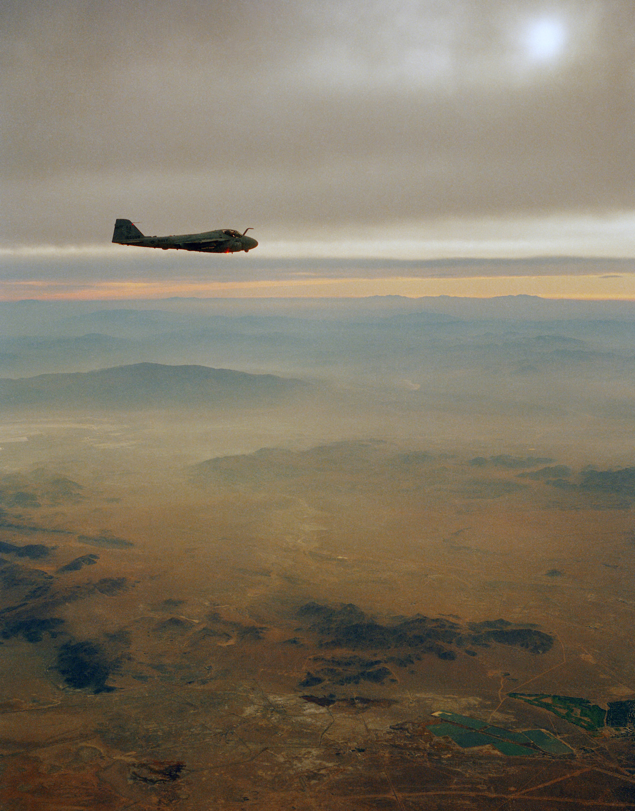An A-6E Intruder aircraft in flight over the Naval Weapons Center, China Lake, California, during an early morning test flight