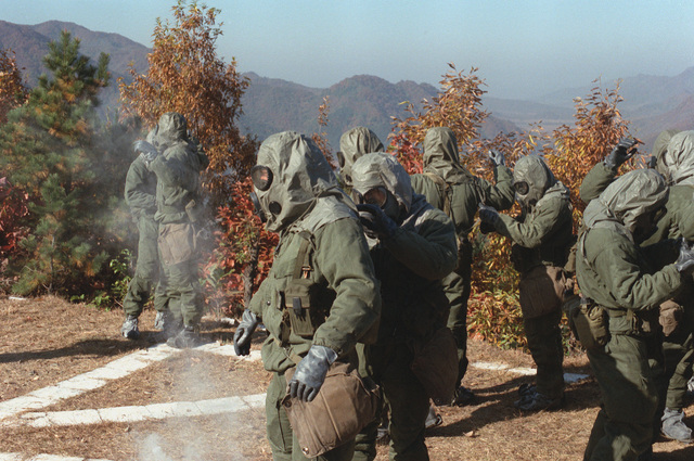 Members of Headquarters Battery, 12th Marines, train for Nuclear, Biological, Chemical (NBC) warfare in Mission- Oriented Protective Posture response level 4 (MOPP-4) gear during the joint Korean-U.S. Exercise Bear Hunt '88