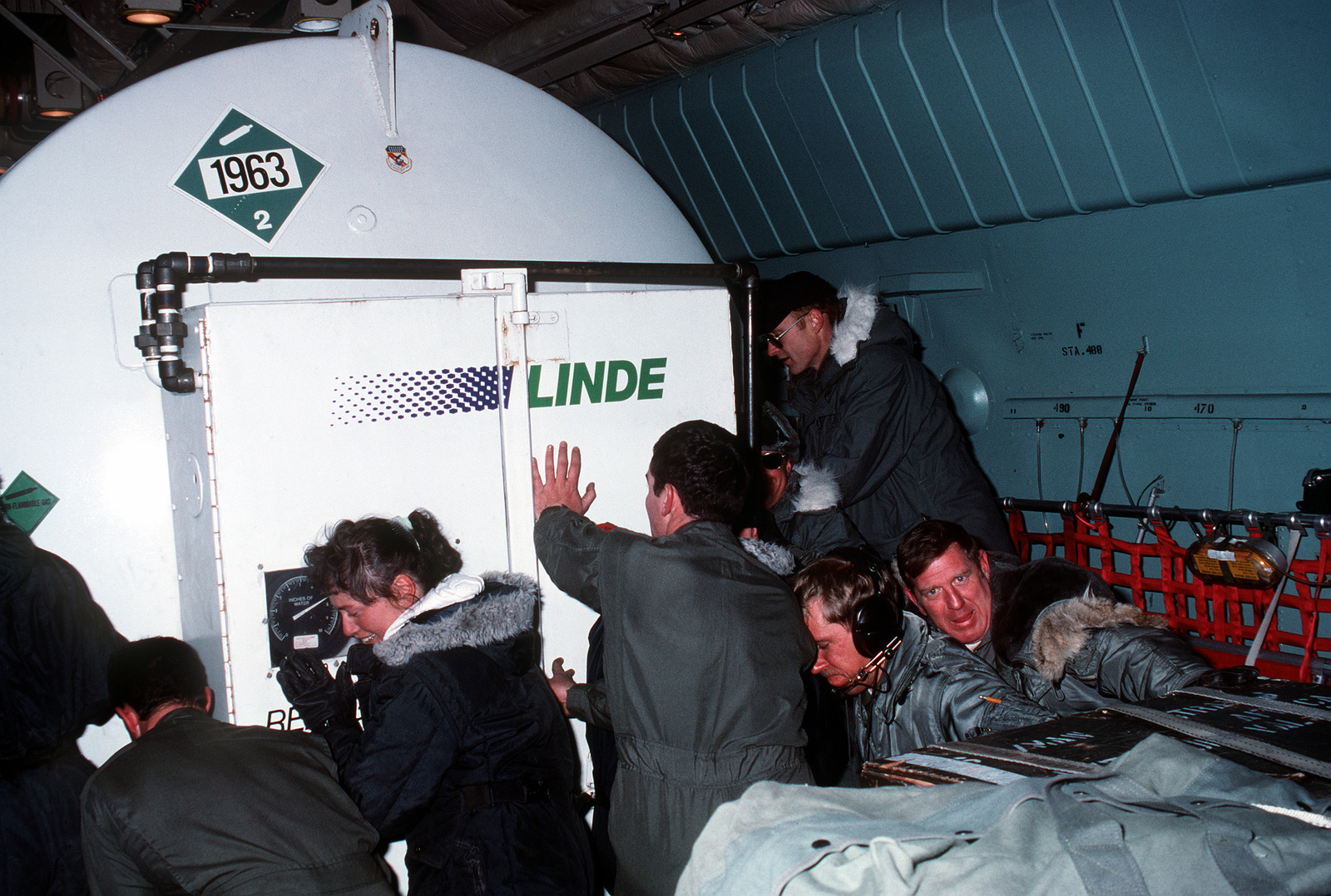 Flight crew and ground crew members pitch in to unload a