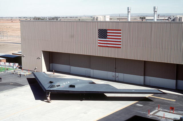 A left front view of the B-2 Advanced Technology Bomber aircraft parked in front of its hangar at Air Force Plant 42 for its rollout ceremony