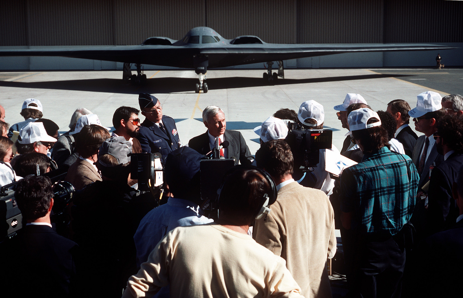 Accompanied by Air Force Public Affairs Director Brigadier General Michael P. McRaney, Secretary of the Air Force Edward C. Aldridge Jr., speaks to journalists at Air Force Plant 42 during the rollout ceremony for the advanced technology bomber
