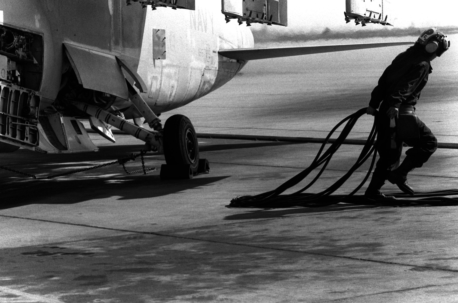 AIRMAN Grisselle Martinez drags power cables away from an A-7 Corsair II aircraft