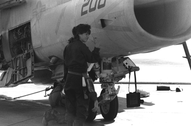 AIRMAN Grisselle Martinez performs a routine inspection on an A-7 Corsair II aircraft