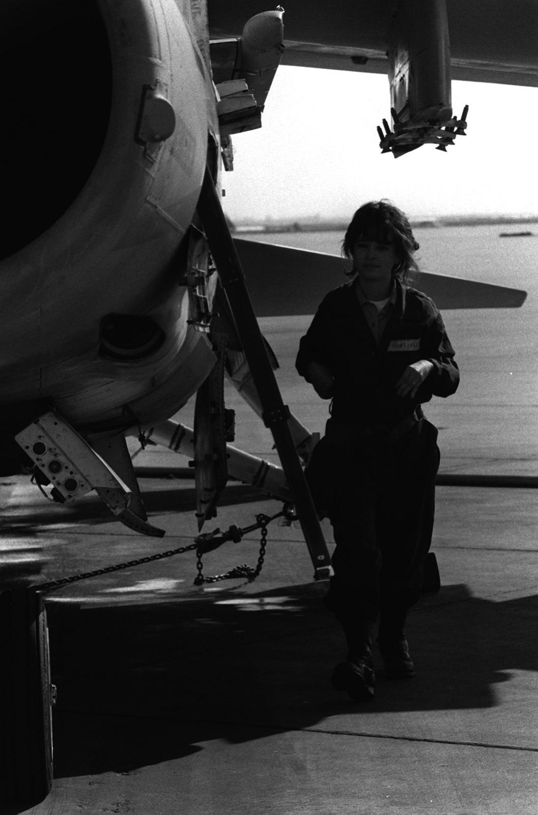 AIRMAN Grisselle Martinez performs a routine maintenance inspection on an A-7 Corsair II aircraft