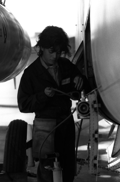 AIRMAN Grisselle Martinez performs routine maintenance on an A-7 Corsair II aircraft
