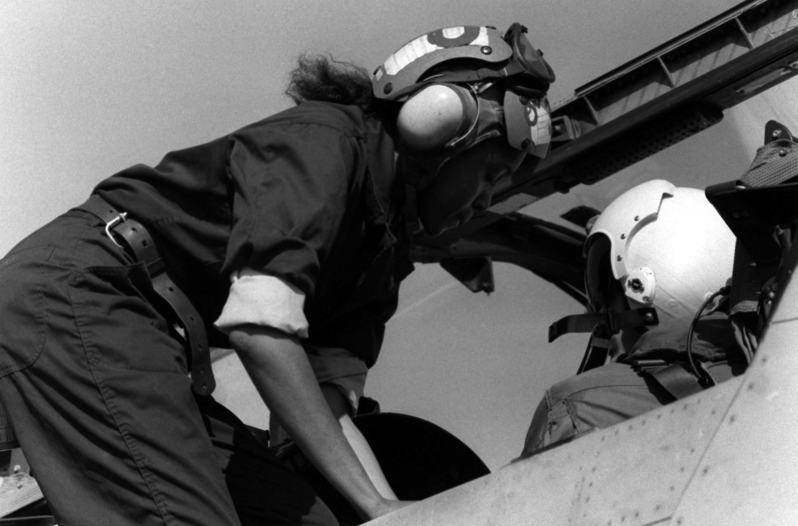 AIRMAN Ora Howard, plane captain, helps secure a pilot into the cockpit of an A-7 Corsair II aircraft
