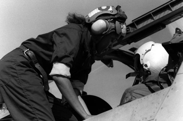 AIRMAN Ora Howard, plane captain, helps secure a pilot into the cockpit of an A-7 Corsair II aircraft