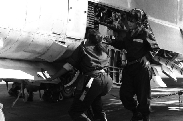 AIRMAN Ora Howard, plane captain, left, and AIRMAN Grisselle Martinez perform a routine inspection on an A-7 Corsair II aircraft