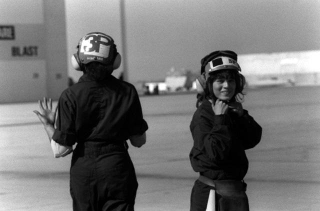 AIRMAN Ora Howard, plane captain, left, and AIRMAN Grisselle Martinez walk along the flight line