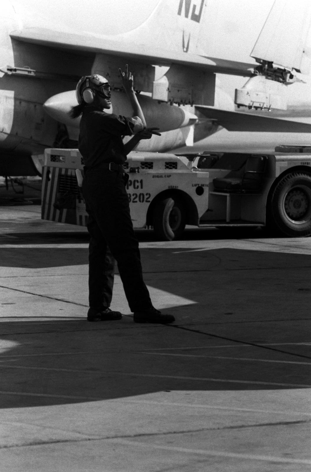 AIRMAN Ora Howard, plane captain, signals instructions to the pilot of an A-7 Corsair II aircraft