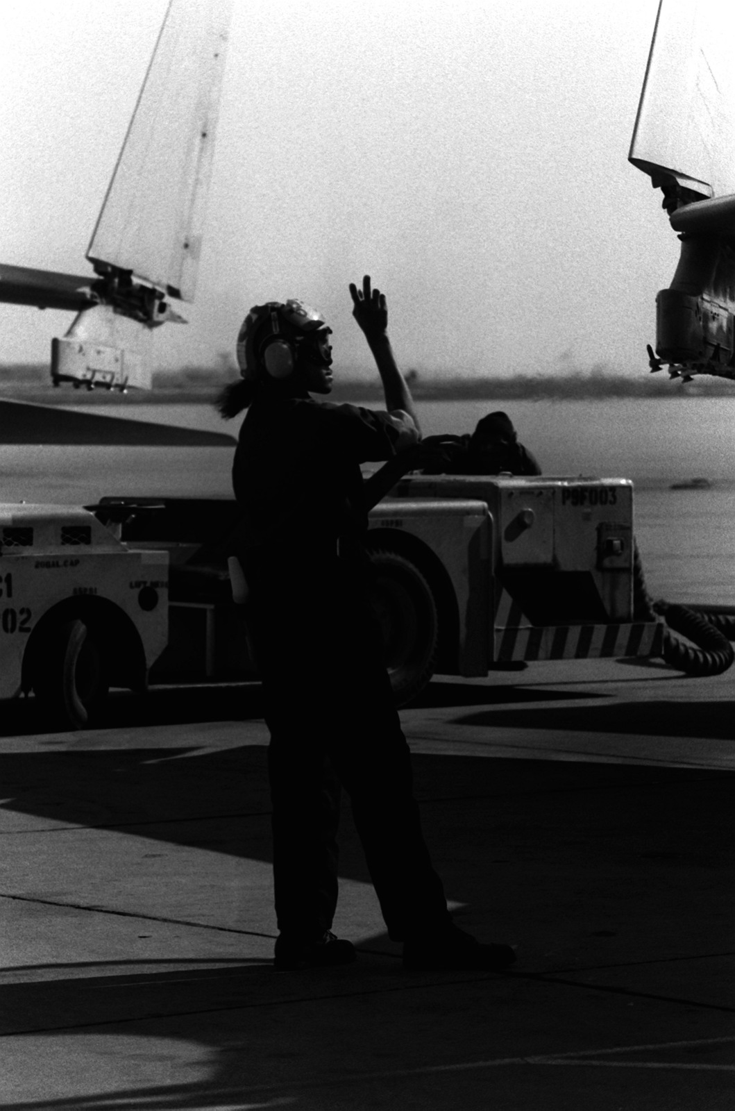 AIRMAN Ora Howard, plane captain, signals instructions to the pilot of an A-7 Corsair II aircraft