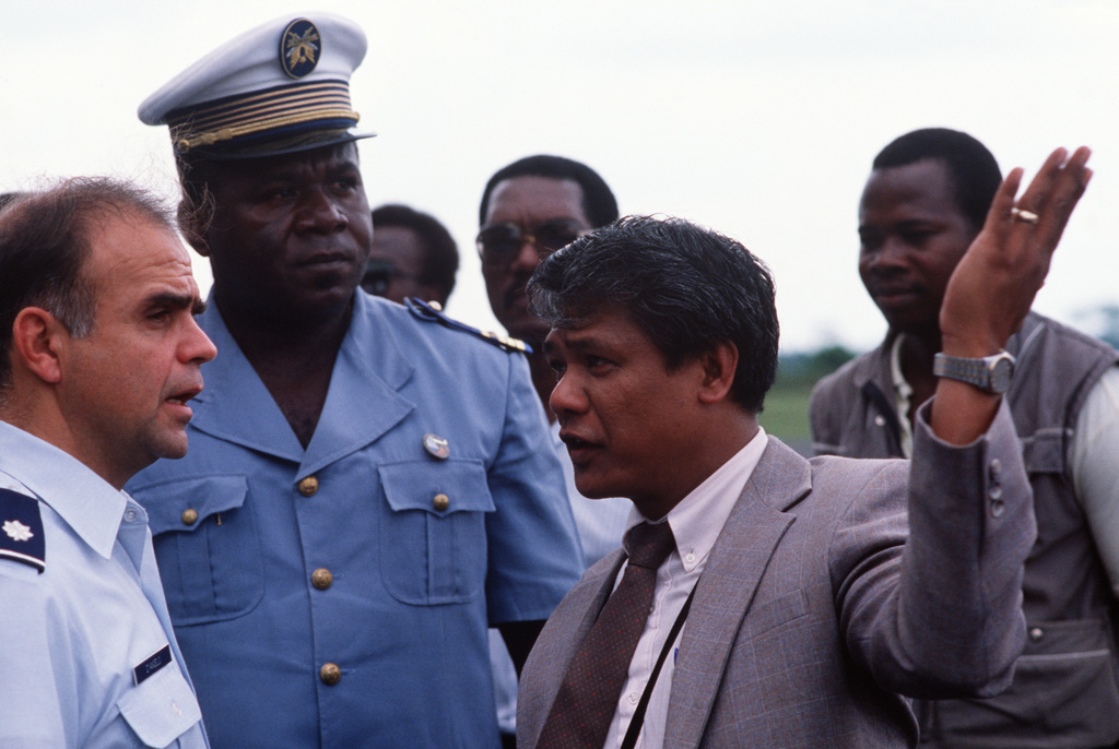 Lieutenant Colonel (LTC) George A. D'Angelo, left, Deputy Director of the Office of Humanitarian Assistance, talks to a community leader with CHIEF Angel R. G. Ceto, center, acting as a translator
