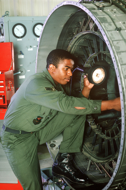 An airman uses a lamp to illuminate the interior of an engine he is servicing