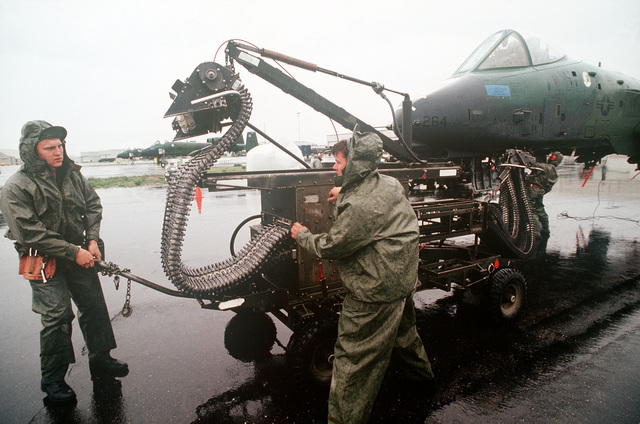 SENIOR AIRMAN Steve Confair, left, and AIRMAN First Class Kirby Lewis of the 343rd Aircraft Generation Squadron remove an ammunition loader from an A-10 Thunderbolt II aircraft as STAFF Sergeant John Sabbadish closes the plane's gun access panel