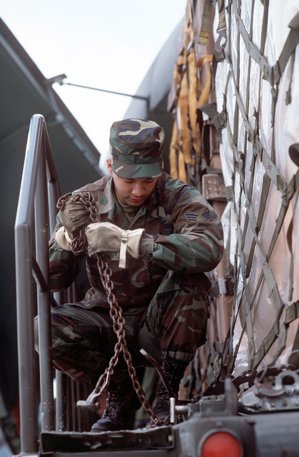 SRA Joe Lee, an air cargo specialist of the 438th Aerial Port Squadron, unlatches a pallet at the top of a K-loader
