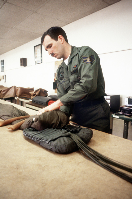 SSGT Hugh McCloskey, non-commissioned officer in charge of the survival equipment section of the 17th Field Maintenance Squadron, inspects a parachute used by TR-1 aircraft pilots of the 17th Reconnaissance Wing