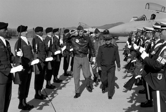 GEN Merrill A. McPeak, center left, commander in chief, Pacific Air Forces (PACAF), salutes as he passes between the ranks of a joint U.S./South Korean air force honor guard upon his arrival at the base. Beside him is MGEN Pak of the South Korean air force. COL Kenneth Ritt, vice commander of Taegu Air Base, walks behind GEN McPeak