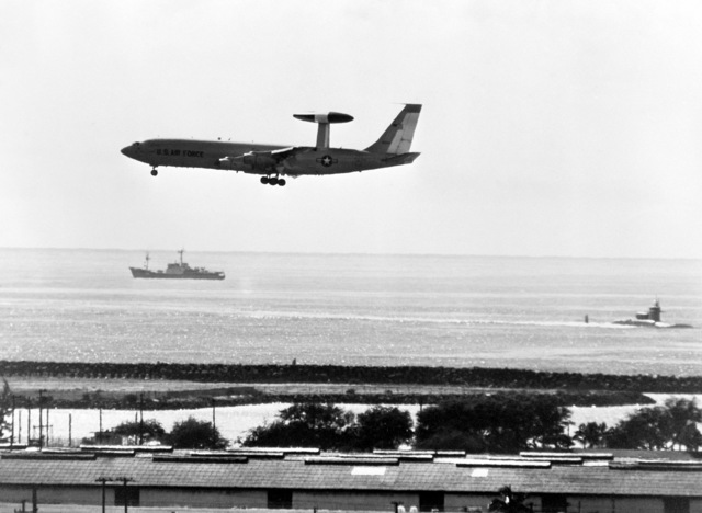 The Soviet navy Moma class intelligence collector SSV 472 passes the entrance to the Pearl Harbor channel as a US Air Force E-3A Sentry aircraft comes in for a landing at Hickam Air Force Base. At left, the nuclear-powered attack submarine USS SAM HOUSTON (SSN 609) heads for Naval Base, Pearl Harbor