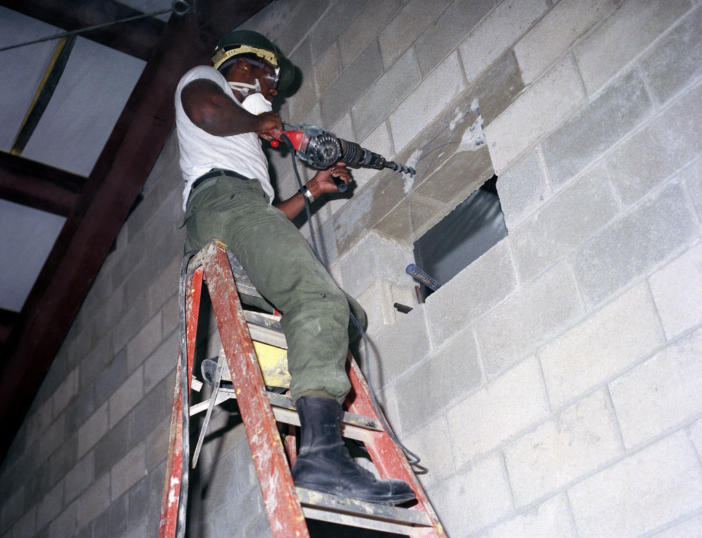 Steelworker 3rd Class of Naval Mobile Construction Battalion 3 (NMCB-3) drills a hole in a concrete block wall to create an opening for an air conditioning duct