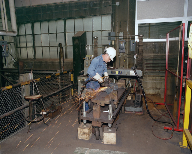 A workman uses a power sander