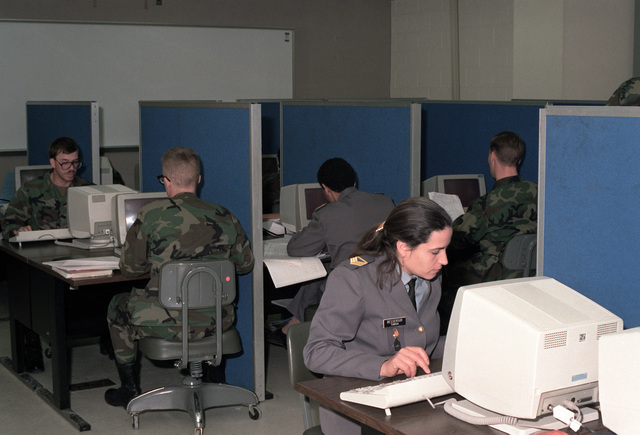 Students in the Basic Computer Systems Operator Course at the Army's new Computer Science School take a test.  In the foreground is a visiting student from the Tunisian military