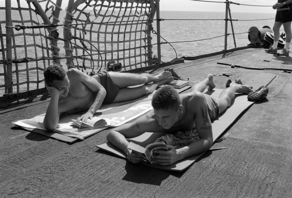 Fire Control Electrician Second Class (FT2) Woods and GUNNER's Mate G (Guns) Third Class (GM3) Immerfall sunbathe during the steel deck picnic aboard the tank landing ship USS SUMTER (LST 1181).  The SUMTER is transiting the Atlantic Ocean on a West African training cruise