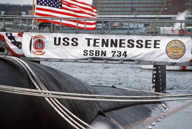A banner with the ship's coat of arms and the seal of the state of Tennessee covers the brow of the nuclear-powered fleet ballistic missile submarine USS TENNESSEE (SSBN 734).  The TENNESSEE, which is being commissioned at the Naval Underwater Systems Center, is the first submarine equipped to carry the new Trident II D-5 missile