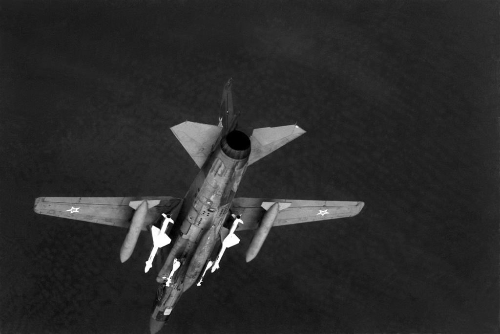 An air-to-air underside view of a Soviet MiG-23 Flogger aircraft. The aircraft is armed with AA-7 Apex missiles on wing pylons and AA-8 Aphid missiles on fuselage stations