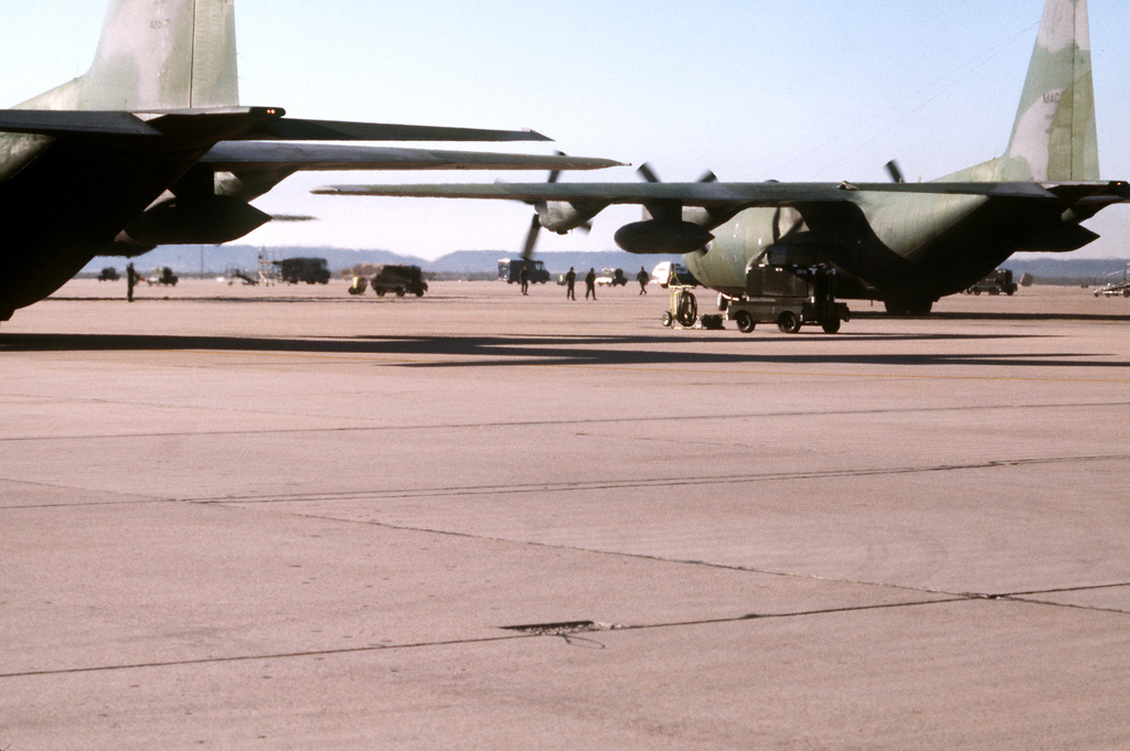 A 463rd Tactical Airlift Wing C-130 Hercules aircraft begins to taxi off the apron at the start of a mass airdrop exercise