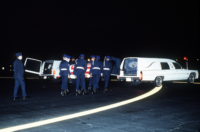 Members of the Dover Air Force Base Honor Guard bear a casket from a C-141B Starlifter aircraft to a waiting hearse. The casket contains the remains of one of six US servicemen killed in December crash of Pan Am Flight 103 in Lockerbie, Scotland