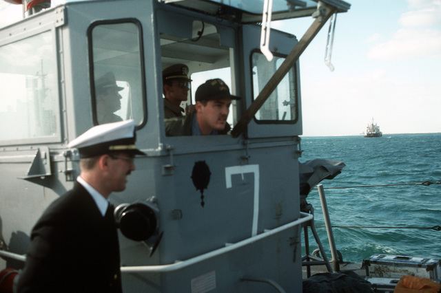 A crewman peers out a propped-open porthole on an LCM 8 mechanized landing craft. The LCM and other navy small craft and warships are in the gulf to provide security for US-flagged shipping