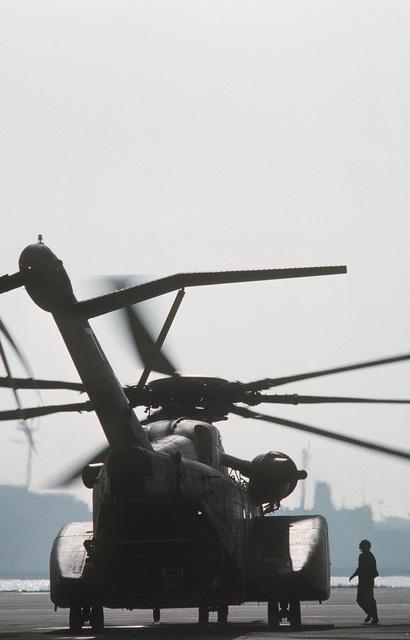 A ground crewman looks over an MH-53E Sea Dragon helicopter from Helicopter Mine Countermeasures Squadron 15 (HM-15) as it idles on the flight line prior to a flight