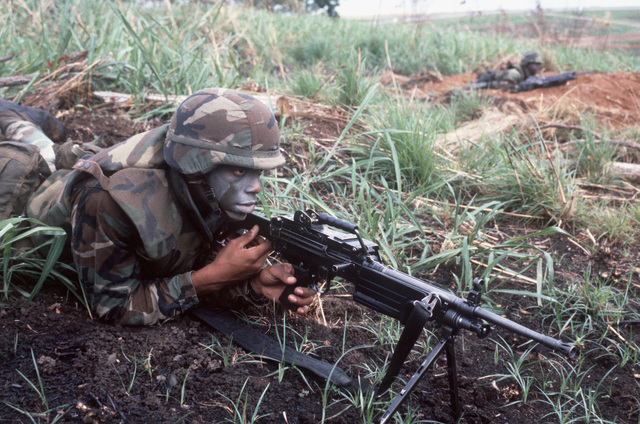 A Marine automatic rifleman mans his M249 squad automatic weapon (SAW) during a joint services exercise