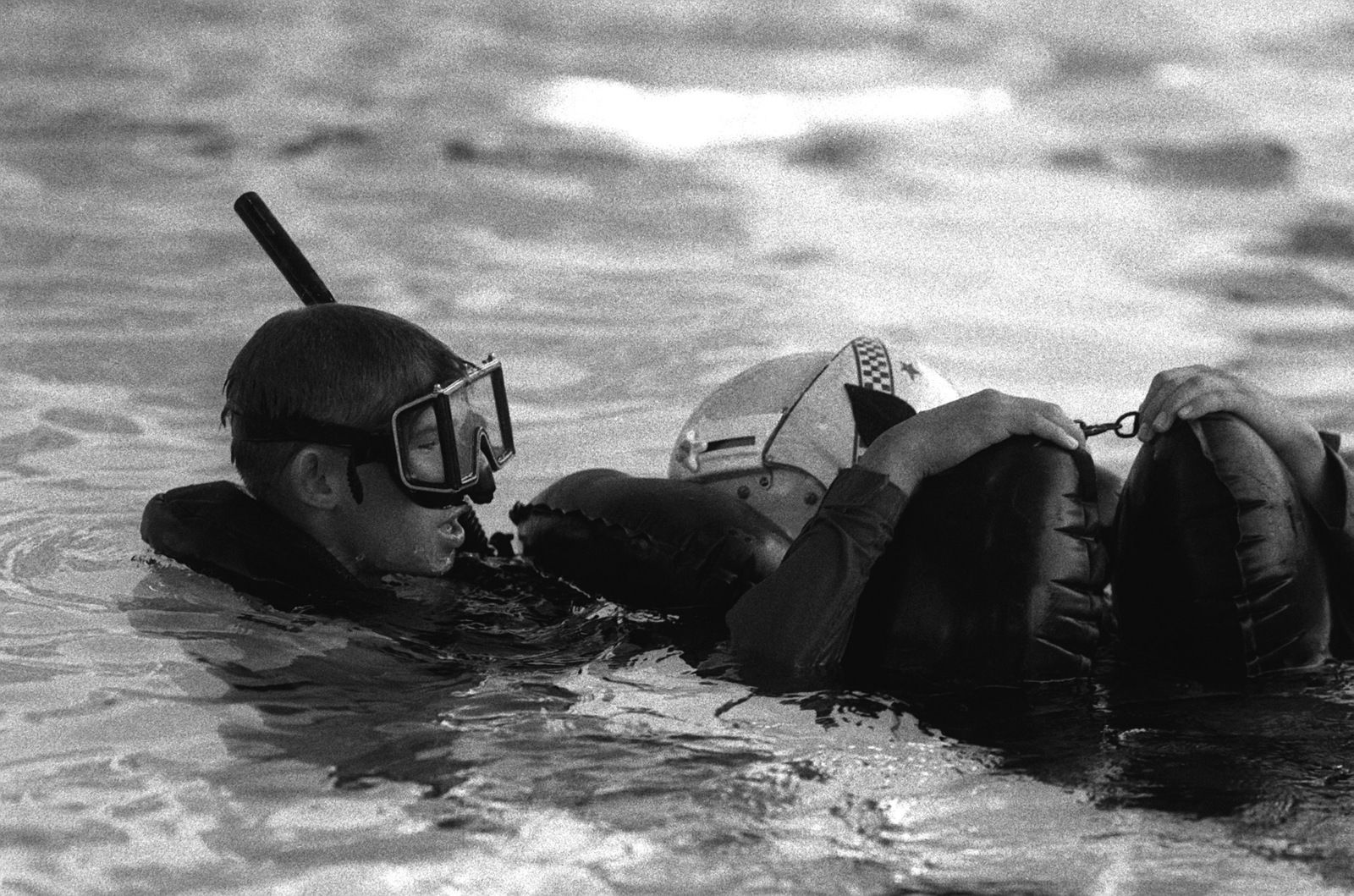 A student comes to the aid of a downed aviator during a simulated rescue, part of the twenty-day, intensive training course at the Navy Rescue Swimmer School. Exact Date Shot Unknown