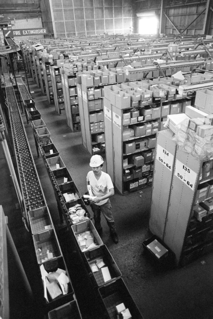 A worker in a Naval Supply Depot warehouse loads small items into baskets that are equipped with coded microchips for for inventory control purposes