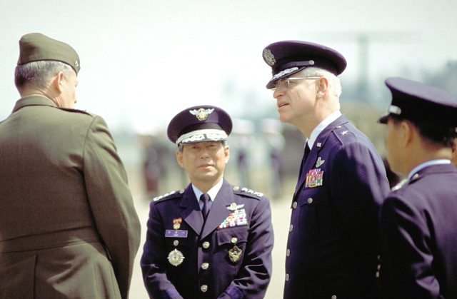 American and Korean flag officers gather prior to a service marking the departure of the remains of 19 Marines killed in the crash of a CH-53 Sea Stallion helicopter during the joint U.S./Korean exercise Team Spirit '89. They are, from left to right, MAJ. GEN. Hollis E. Davison, assistant chief of staff, Republic of Korea Combined Forces Command; LT. GEN. Han Cha Sok, CAC commander; and Brig. GEN. Peter Hayes, vice commander, 7th Air Force