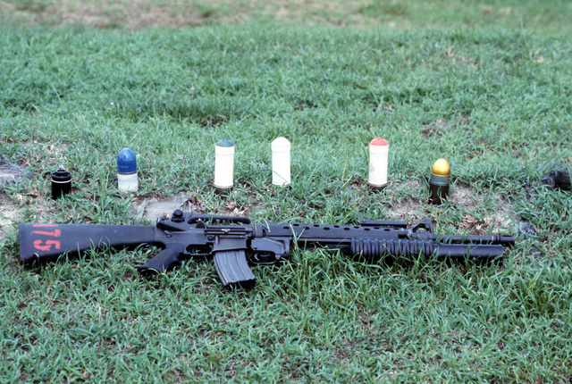An M16A2 rifle equipped with an M203 grenade launcher lies in the grass near some of the types of 40 mm ammunition available for use with the M203. The cartidges are, from left to right, multiple projectile, practice, green star flare, white star flare, red star flare and high explosive