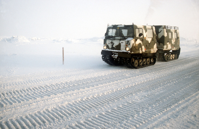 An M973 small unit support vehicle (SUSV) makes its way to the exercise area down a snow-covered road during Exercise BRIM FROST '89