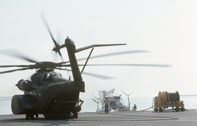 An MH-53E Sea Dragon helicopter from Helicopter Mine Countermeasures Squadron 15 (HM-15) idles on the flight line as it waits for the signal to take off on a minesweeping exercise.  Beyond the helicopter is a Mark 105 minesweeping sled that will be used in the exercise