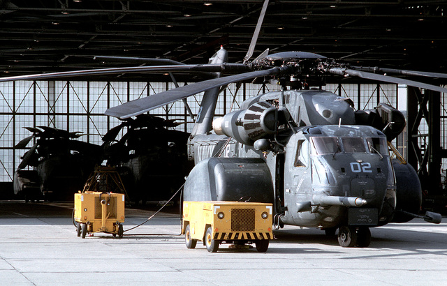 An NC-8A mobile powerplant and a hydraulic test stand sit beside an MH-53E Sea Dragon helicopter from Helicopter Mine Countermeasures Squadron 15 (HM-15) outside a hangar containing two other Sea Dragons