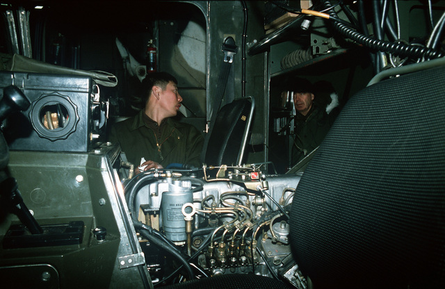 Brigadier General William Fareman, right, of Forces Command (FORSCOM), J-4, watches a soldier from the 706th Maintenance Battalion working on the engine of an M973 small unit support vehicle (SUSV) during Exercise BRIM FROST '89