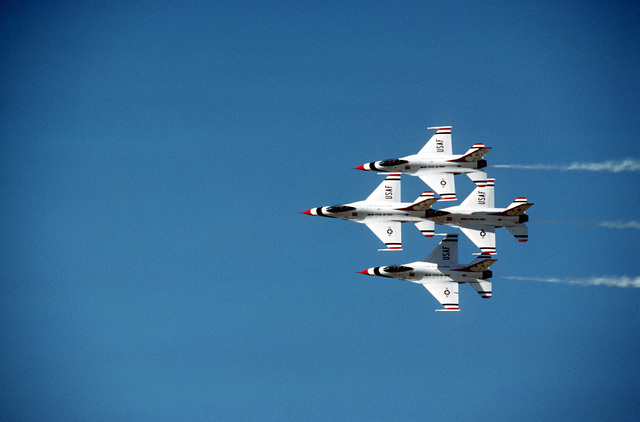 F-16A Fighting Falcon aircraft execute a difficult maneuver during a performance by the Thunderbirds, the U.S. Air Force Flight Demonstration Squadron. The Thunderbirds are performing during an air show, part of the base's annual open house